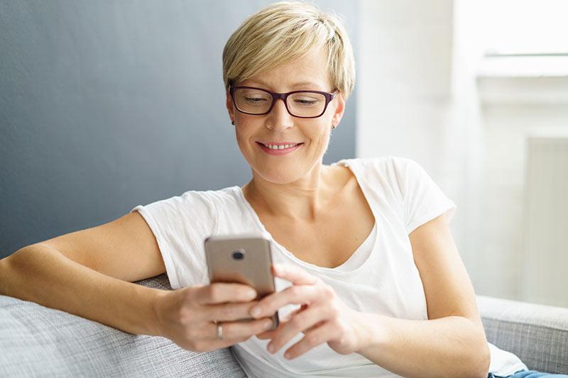 Frau googelt am Handy Service für Elektrotechnik im Raum Stuttgart