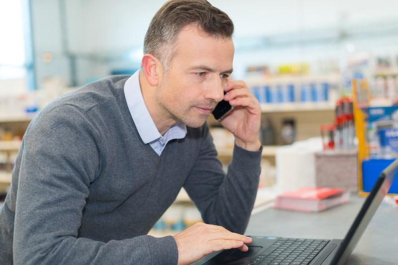 Mann am Telefon spricht über die Wartung von Werkzeugmaschinen